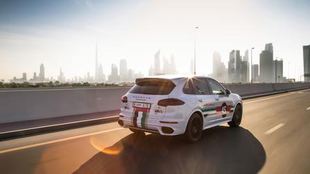 Porsche In Dubai, against a bright Dubai skyline